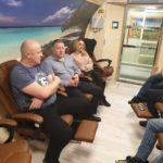 grupa osób siedzących w komorze normobarycznej w trakcie tlenoterapii